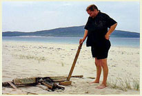 mike bannister on a beach.. with a stick